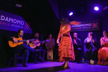Tanečnica flamenca s gitaristami a spevákmi v pozadí, na pódiu v madridskom tablao