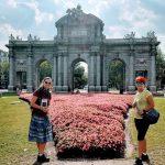 Vstupná brána do Madridu Puerta de Alcalá a rozkvitnutý záhon ruží s klientami v lete